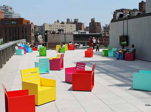 Colorful chairs outside of a downtown art museum in New York on a clear summer afternoon.