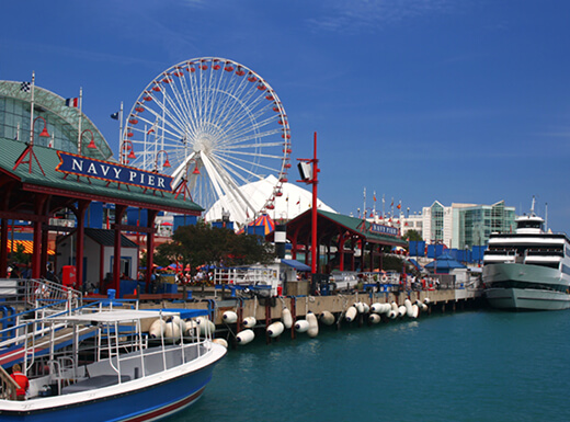 Boats are docked along the Navy Pier landmark and ferris wheel in Chicago on a sunny morning.