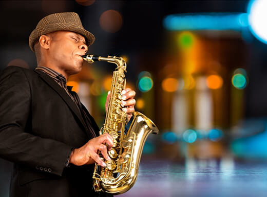 A man wearing a tan hat plays a saxophone at night in Greenwich Village in New York City.