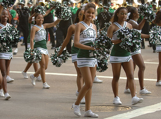 A squad of cheerleaders wearing white and green uniforms walk in Houston's Thanksgiving Day Parade while cheering with pom poms.