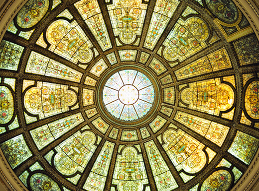 A view looking up at the artistic stained glass ceiling of the Chicago Cultural Center.