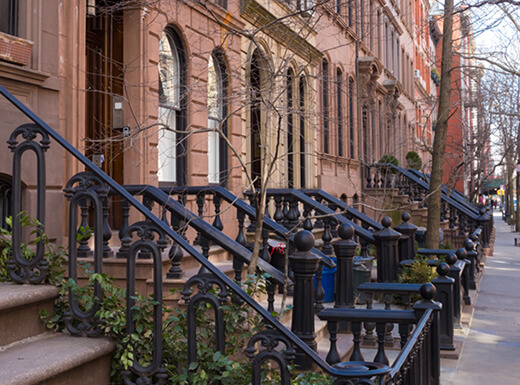 Sidewalk view of brownstones and iron railings in Greenwich Village, NYC, on an overcast morning.