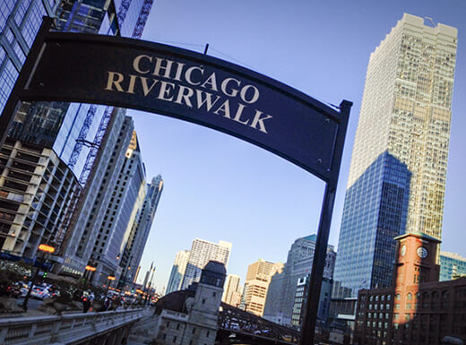 The Chicago Riverwalk entrance sign is photographed in the shade on a sunny day.