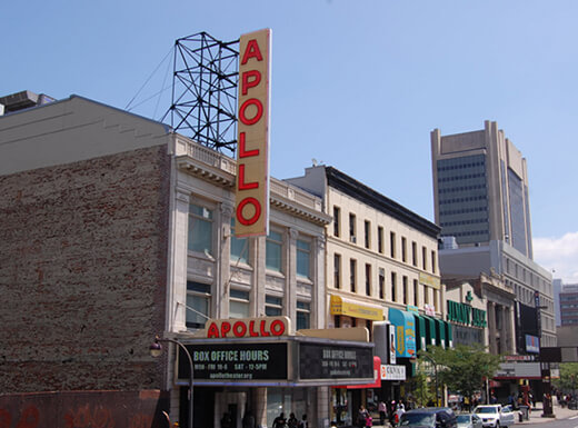 Exterior view of the Apollo Theater in New York City under blue skies on a summer afternoon.