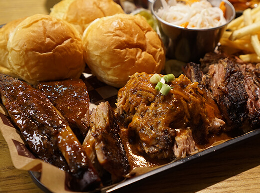 Up close view of fresh BBQ ribs, crispy golden fries, crunchy coleslaw, and dinner rolls at a local barbecue restaurant in Texas.