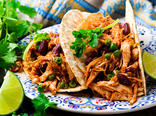 Two Tex-Mex soft tacos on a blue and white plate with a lime garnish on the side wait to be enjoyed at lunchtime.