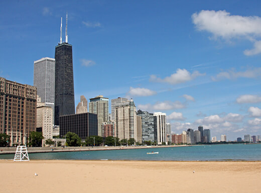 A sunny beach area of Lake Michigan on a spring afternoon with Chicago's city skyline in the background.