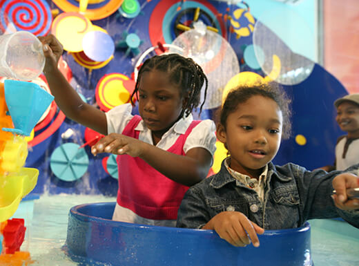 Two kids play and learn in the interactive exhibits at Brooklyn Children's Museum on a busy morning.