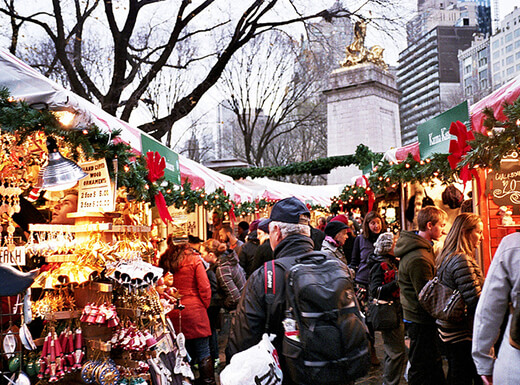 Crowd of people shopping in a NYC holiday market on a gray winter morning.
