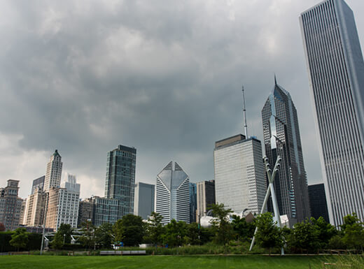 View of Millennium Park under a dark, cloudy sky on a rainy morning with the skyline in the background in Chicago, Illinois.