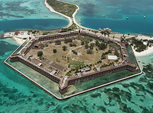 Aerial daytime view of Fort Jefferson, Dry Tortugas National Park in Florida shows beautiful shallow ocean waters surrounding the islands with white sand beaches.