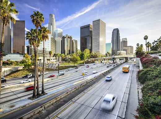 Downtown cityscape view of Los Angeles, California with a busy freeway highway in the forefront.