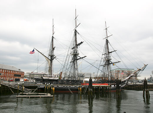 The USS Constitution Navy warship, part of the Freedom Trail, sits on the dock in Boston on a grey, cloudy day.