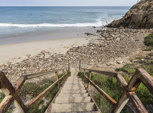A rusted, metal stairway leading down toward Dume Cove, Malibu, CA on sunny afternoon shows the rocky and sandy beach along the shore of the beautiful Pacific Ocean.