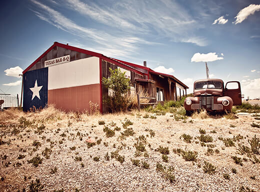 Exterior view of South-Central Texas BBQ restaurant under blue skies in the desert.
