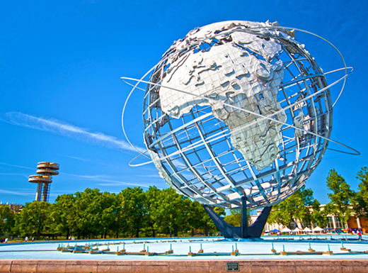 The Unisphere at Queens' Flushing Meadows Corona Park is seen among green trees under a blue sky on a bright afternoon.