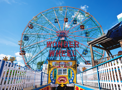 The colorful Ferris wheel at Coney Island amusement park sits beneath a bright summer sky on a sunny afternoon.