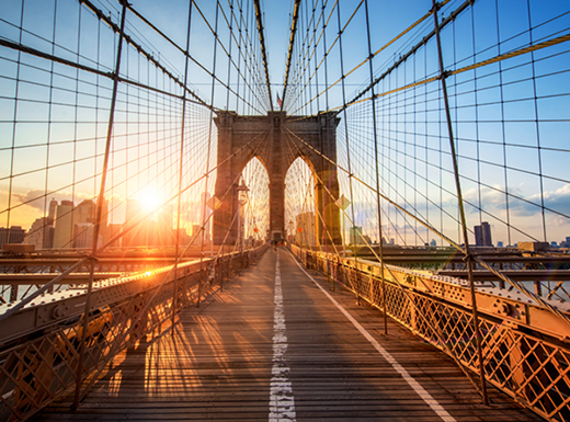 View of the Brooklyn Bridge walkway at sunset in New York City during a golden evening.