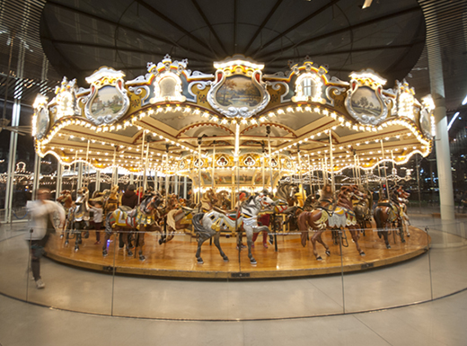 View of the brightly lit Jane's Carousel in DUMBO, Brooklyn with visitors riding on the carousel ponies.