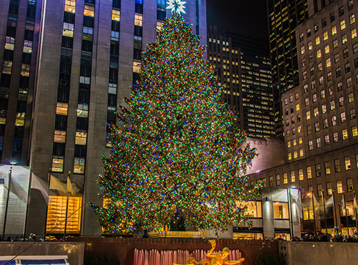 A nighttime view of the giant, decorated Christmas tree at Rockefeller Center in NYC with lighted buildings surrounding it.