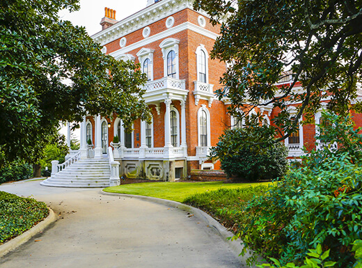 A treed driveway leads to the Johnston Felton Hay House in Macon, Georgia, a stately large brick mansion with white trim and a white front porch.