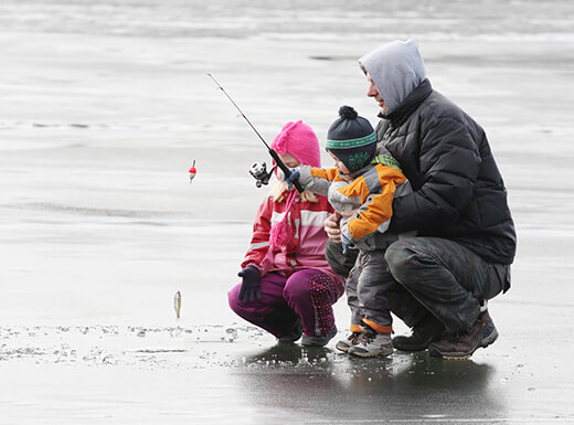 A father wearing a black winter coat teaching his two children how to ice fish at Lake Winnibigoshish in Minnesota on a cloudy afternoon.