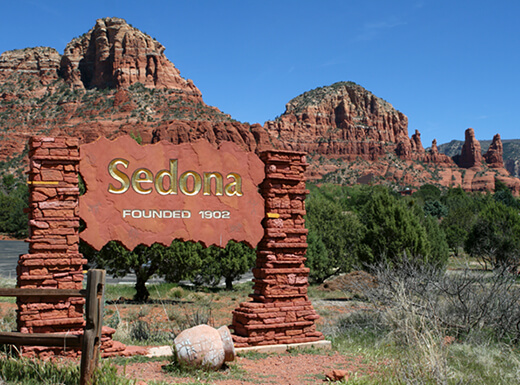 Red rock sign for Sedona, founded 1902, with shrubbery and mountains in the background, just a short drive from Phoenix.