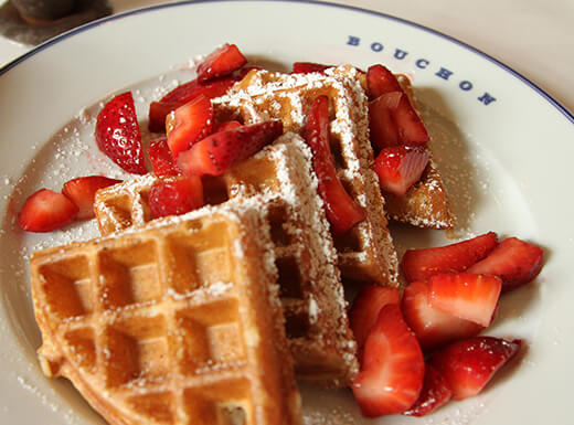 A waffle with syrup, powdered sugar, whipped cream topping, and red strawberries during brunch at the Bouchon at The Venetian in Las Vegas, Nevada.