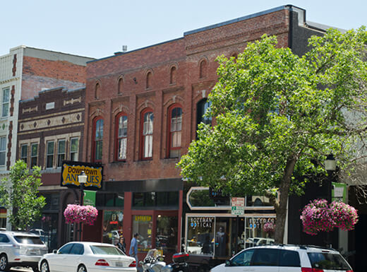 The south side of East Main Street in Bozeman, Montana, showing brick storefronts and parked cars on a sunny spring day.