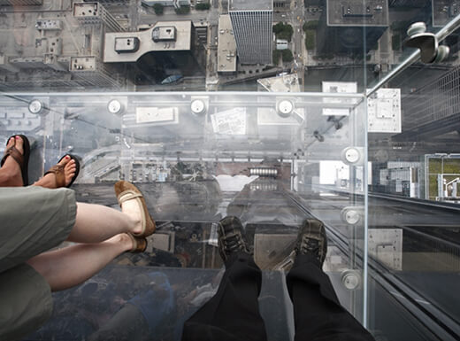 Three people standing on a see-through observation deck hundreds of feet above Chicago's downtown on a spring morning.