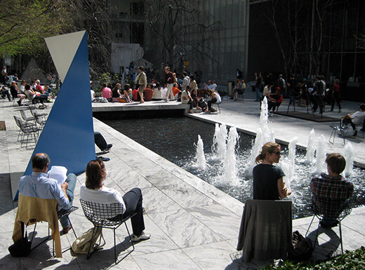 People enjoying a beautiful summer afternoon by the fountain in front of the Museum of Modern Art in NYC
