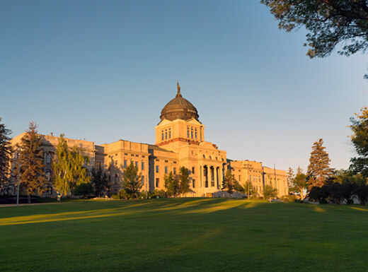 Angled view of the Capitol Building in Helena, Montana, a white stately building with a tall spire in the middle, drenched in the early evening sun surrounded by trees.