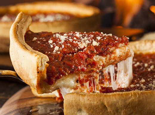 A close-up shot of a slice of Chicago-style deep-dish pizza being served at lunchtime in downtown Chicago.