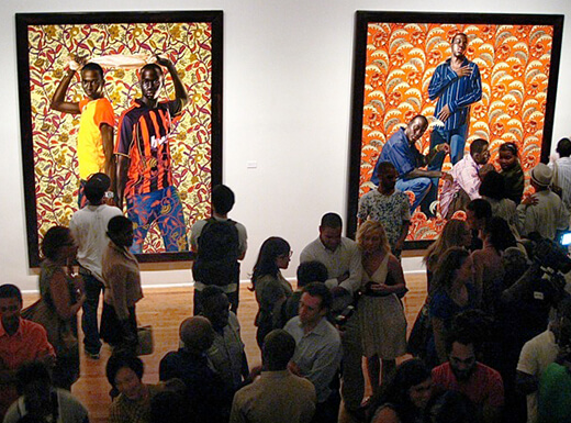 People enjoying the colorful art by Kehinde Wiley hanging on the walls of the Studio Museum of Harlem.