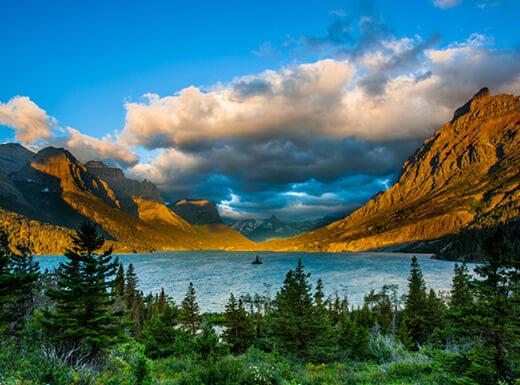 Picturesque view of St. Mary Lake at Glacier National Park from Wild Goose Island at sunrise in Montana showing the sun shining on the mountains and the light blue water lined with green pine trees.