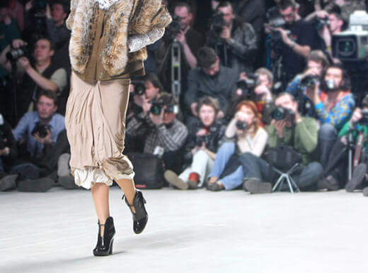 A fashion model walks the runway at Fashion Week in New York City wearing a long skirt and faux fur coat.
