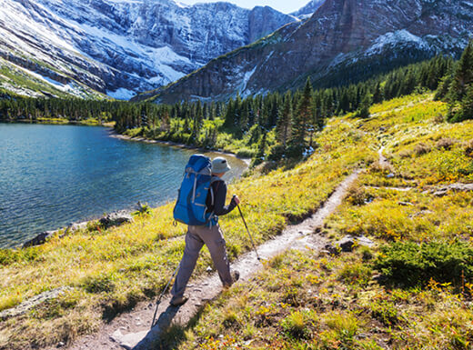 Hiker wearing a hat and large blue backpack uses a walking stick while following a hiking trail toward mountains dusted in snow and pine trees along the shore of a lake in Glacier National Park on a sunny day.