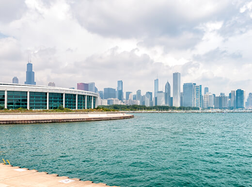 Chicago's Shedd Aquarium with Lake Michigan in the foreground and Chicago's skyline in the background is photographed on a cloudy early morning.