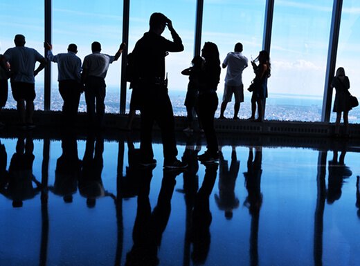A silhouette view of visitors looking out the windows of One World Trade Center in NYC on a bright afternoon.