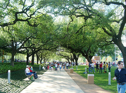 People enjoying the paved walkway under large trees at Houston's Discovery Green Park on a sunny summer afternoon.