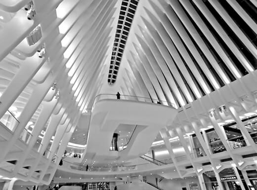 An upward view of the black and white interior of the Oculus in New York City.