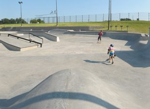 A group of teens skating at the concrete North Houston Skatepark on a sunny afternoon.