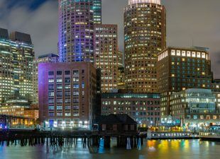 The skyline and building lights of Boston reflect over the Boston Harbor on a partly cloudy night.