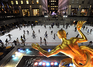 Groups of people skating at Rockefeller Center in NYC on a cold winter night with a gold statue nearby.