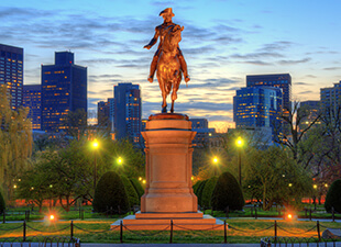 George Washington statue lit up at dusk in the Boston Public Garden, part of the Freedom Trail, with the Boston skyline in the background.