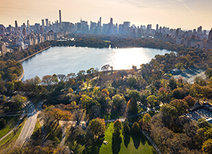 Panoramic aerial view of New York City from above Central Park shows the skyline during the early evening on an autumn day.