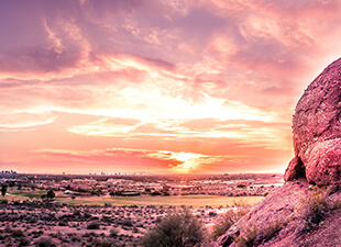 Colorful orange, pink, and purple sunset over Phoenix, AZ shows desert landscape and a golf course view from behind rocks in the early evening.