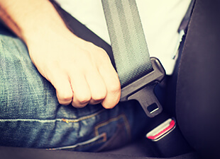 A new driver wearing jeans and a white shirt uses one hand to buckle their seatbelt in the car.